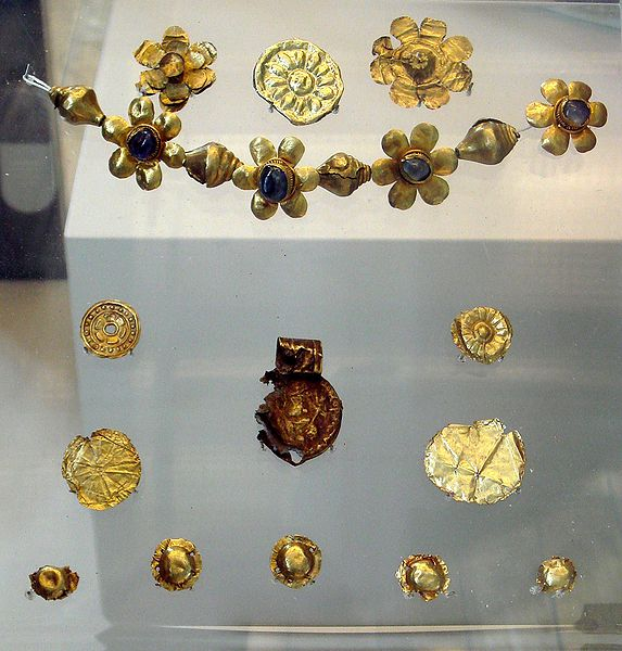 """Offerings found in Bodh Gaya under the """"Enlightenment Throne of the Buddha"""", with a decorated coin of the Kushan emperor Huvishka, 3rd century AD. British Museum."""